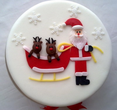 A single layered cake with adorable Santa Claus on top