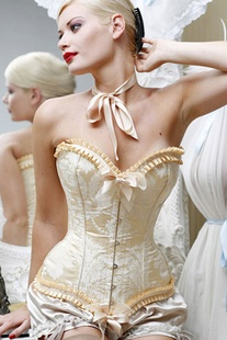 Corset in cream cinches the waist, reminiscent of the Victorian era. #danzitup