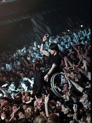 Το κοινό σηκώνει νεαρό σε αναπηρικό καροτσάκι για να μπορέσει να δει τη συναυλία του αγαπημένου του συγκροτήματος
