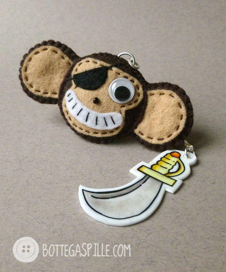 All'arrembaggio!! Una scimmia pirata in avvistamento! Curiosa e biricchina con la sua benda all'occhio, il suo sorrisetto e i suoi piercing non lascia dubbi, è venuta a prendere quanto più oro possibile! Con sè ha portato la sua scimmitarra in polyshrink disegnata a mano. attenzione!