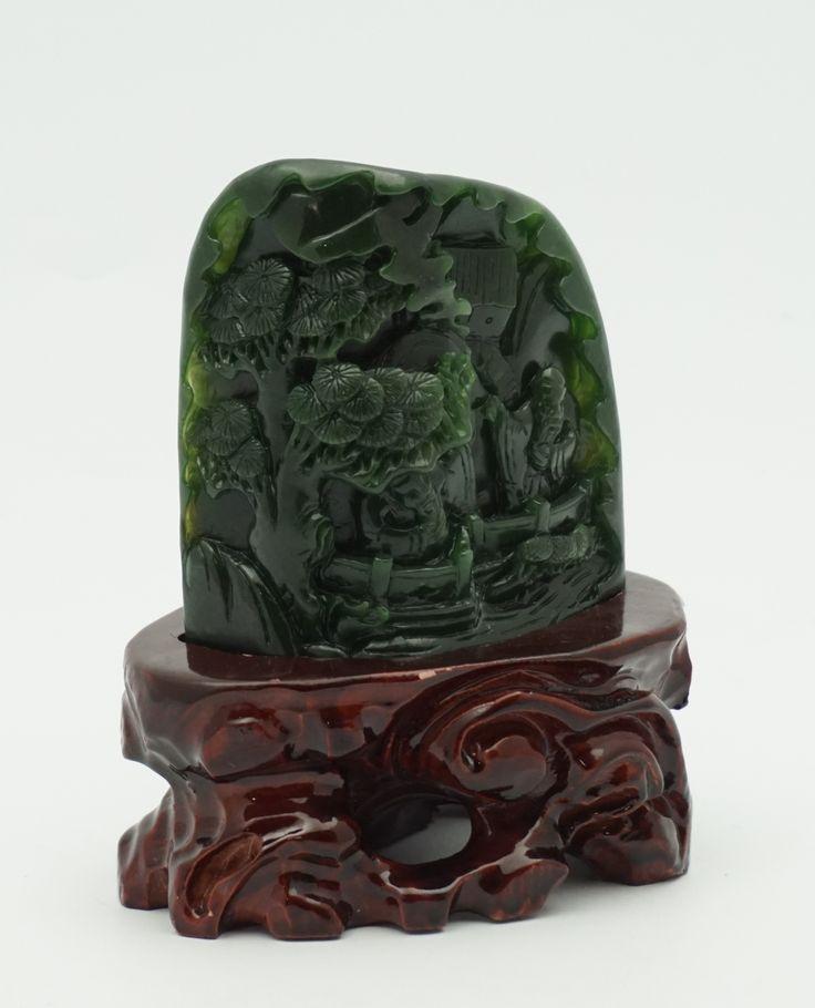 Een groen jade sierstuk met gesneden decor van twee wijsgeren in tuin, op houten voetstuk, China
