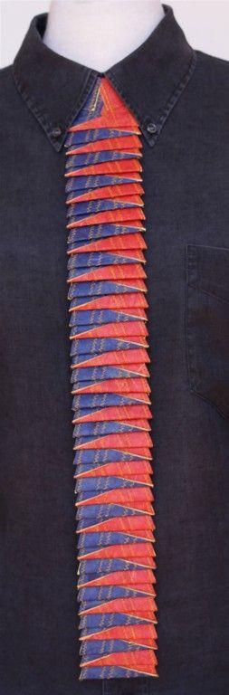 Luis Acosta.  Las corbatas  de papel están confeccionadas con la repetición de una sola forma.  La rigidéz está dada según la cantidad de capas de papel que se han cosido juntas, siendo estas de distintos colores que a veces se acentúan con cintas de seda. distintos tipos de papel, seis capas de papel cosido,  52 x 6 cm,  2006-2008