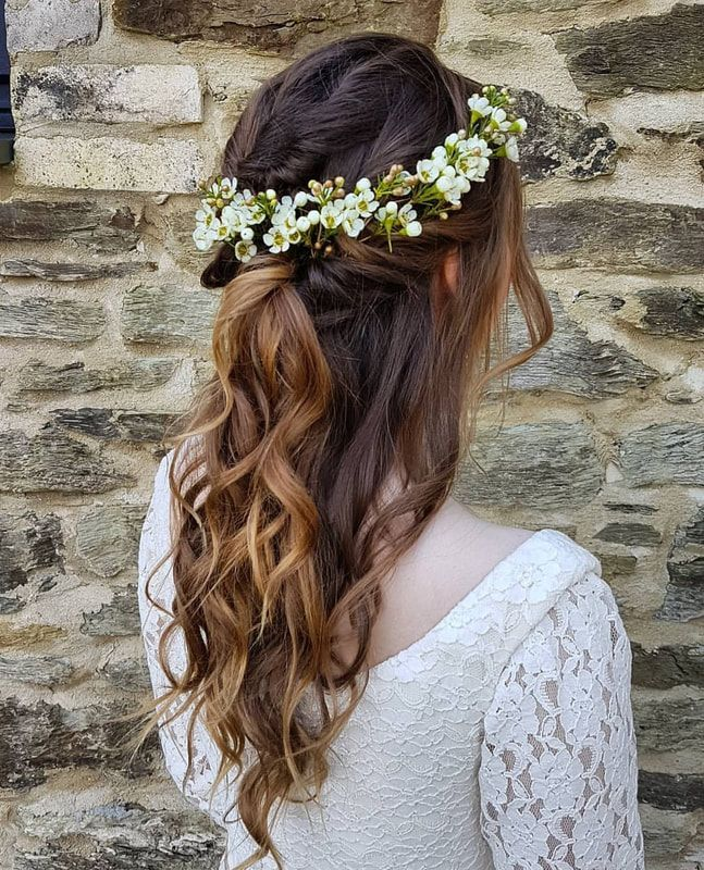 Boho half up half down beachy hairstyle with flowers the perfect bridal hairstyle and a popular option for the relaxed boho bride with soft wavy hair