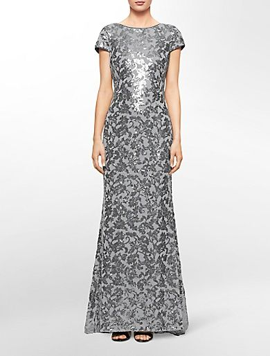 a low draping back adds a sensual touch to this cap sleeve gown with a floral sequin design.