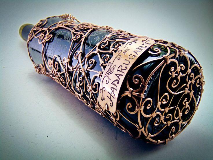 Acoperirea diferitelor obiecte din sticla cu sarma de arama se face prin lovire cu ciocanul direct pe sticla.Precizez ca nu folosesc cositor sau alte modalitati de lipire , sudura , doar ciocanul si clestele. O sticla de vin  acoperita cu sarma de arama are prinsa pe ea intre 160 si 550 de nituri .Fiecare nit de arama este executat manual , respectiv batut pe rand fiecare cu ciocanul direct pe sticla cu vin, imbinand modelele unice din sarma de cupru.