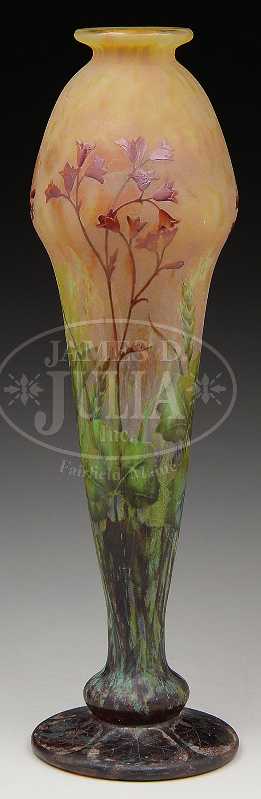 "DAUM CAMEO AND ENAMELED VASE. Daum vase has a round foot with brown cameo lily pads surrounding the top. The vase is further decorated with vitrified cameo glass stems and leaves surrounding the bottom half of the vase in shades of green and brown. Slender stems rise to support bell flowers all against a slightly mottled yellow and orange background. The stems and bell flowers are enameled in shades of red. Signed on the side in cameo ""Daum Nancy"" with Cross of Lorraine."
