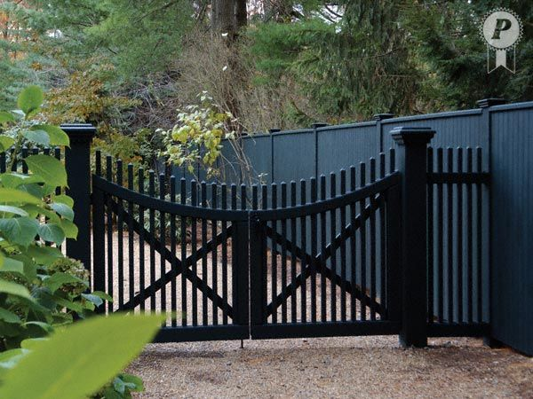 Majestic style enhances this beautiful scalloped Mt. Vernon double drive gate, featuring a scalloped top rail to match. These gate leaves are hung from stately pillars. Designer Traditional fencing follows the property line.