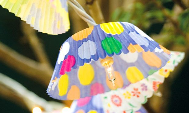 """Se a festa for à tardinha, ilumine o ambiente com um toque inusitado: uma luminária-móbile feita de luzinhas pisca-pisca e cúpulas de formas de cupcake. Faça um pequeno corteem """"x"""" no fundo da forminha e passe o bico de luz por ele. Escolha três estampas diferentes de forminhas e intercale-as na luminária"""