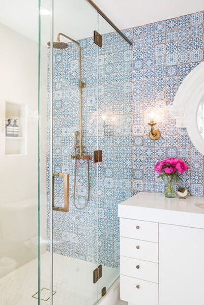 Modern bathroom with blue mosaic tile, gold accents, and a white vanity