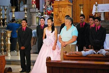"""A Mexican quinceañera after mass in church. Quinceañera (Spanish pronunciation: [kinseaˈɲeɾa]; feminine form of """"fifteen-year-old""""), also called fiesta de quince años, fiesta de quinceañera, quince años, quinceañero or simply quince, is a celebration of a girl's fifteenth birthday with cultural roots in Latin America but celebrated throughout the Americas. This birthday is celebrated differently from any other as it marks the transition from childhood to young womanhood."""