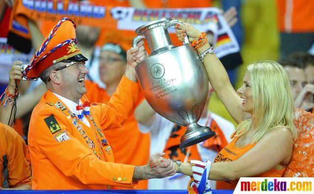 Suporter Belanda bersorak membawa sebuah replika trofi piala Eropa saat laga Belanda melawan Jerman di Stadion Metalist, Kharkiv.
