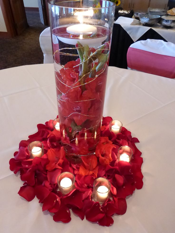 A submerged centerpiece created with red gladiola stems and gold wire surrounded by the glow of candles, loose glad blooms and a rich carpet of red rose petals...a wow luxe look!