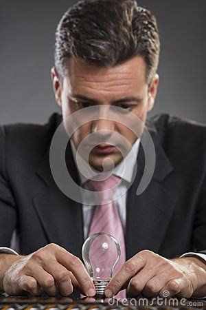 Handsome elegant businessman thinking of smart business solution while holding a light bulb with both his hands. Selective focus on hands and bulb.
