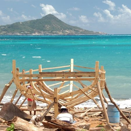 On Carriacou, a small island that makes up part of Grenada, boat-building is still done the old fashioned way -- waiting for some money to come in so you can build  a little more.  BigStock photo.