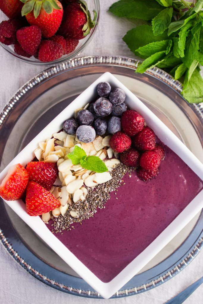 This Bright Berry Acai Smoothie Bowl is made with fruit, acai berry puree, and Greek yogurt that is finished with a fun and colorful variety of toppings. simplylakita.com #smoothie #smoothiebowl #healthy