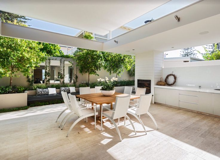 I love the raised roof on this alfresco which enables a view to the sky above. The landscaping provides trees to disguise the wall and mirrors to enlarge the space. The bench seat and retaining wall soften the line of the boundary wall and provide a lovely focal point.  Photo credit- Liz Prater Design