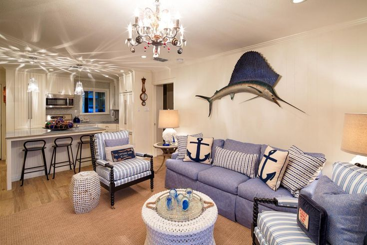 The wood grain porcelain tile floors are soften by a natural fiber rug in the living room. Blue and white upholstered furniture plays into the coastal palette, while nautical elements –– the mounted marlin and anchor throw pillows –– crank the seaside theme up a notch.