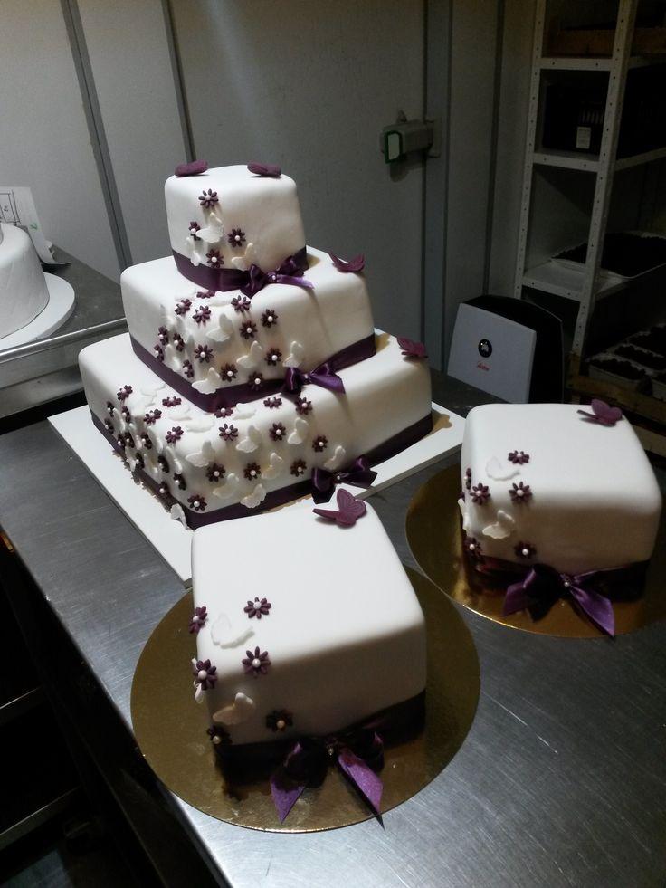 Něžný třípatrový svatební dort potažený fondánem, dozdobený švestkovými květinkami, se kterými kontrastují bílí motýlci a jednoduchá saténová stuha. Ve stejném ladění pak byly i dva děkovací dortíky.