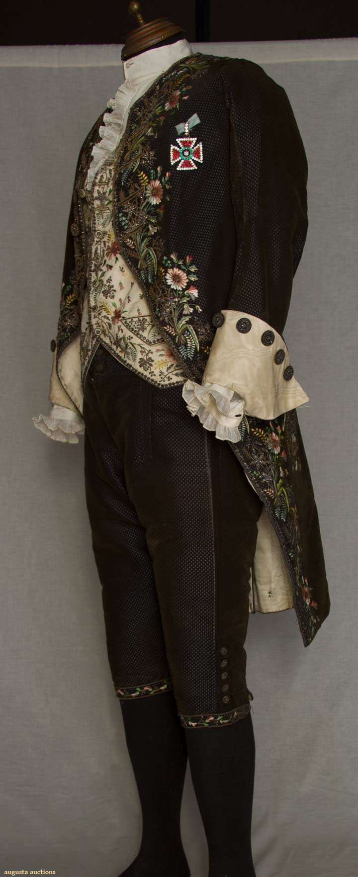 GENT'S FOUR PIECE FORMAL COURT SUIT, c. 1820. Coat & breeches of dark brown cut/uncut velvet to blue satin ground; coat embroidered in polychrome silk large scale florals, gold metallic cord & crimped foil flowers, 20th C. Maltese cross paste insignia coat collar & original cuffs removed.