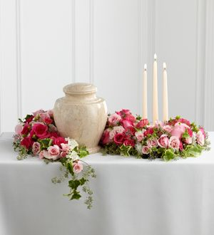 Arrangement is a sweetly sophisticated way to display their urn at their final farewell service. Fuchsia and pale pink roses and spray roses are accented with lush greens to form an exquisite arrangement that winds around the base of the urn and curls around 3 ivory taper candles, creating a warm and comforting presentation that commemorates a life that brought kindness and beauty in to the lives of others.