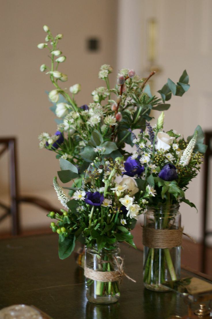 Rustic flower filled jars and bottles for table at Winton House February wedding The Stockbridge Flower Company