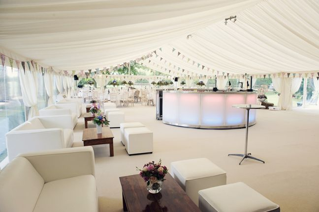 Soft pastel summer wedding marquee. Bunting, illuminated bar and English roses.