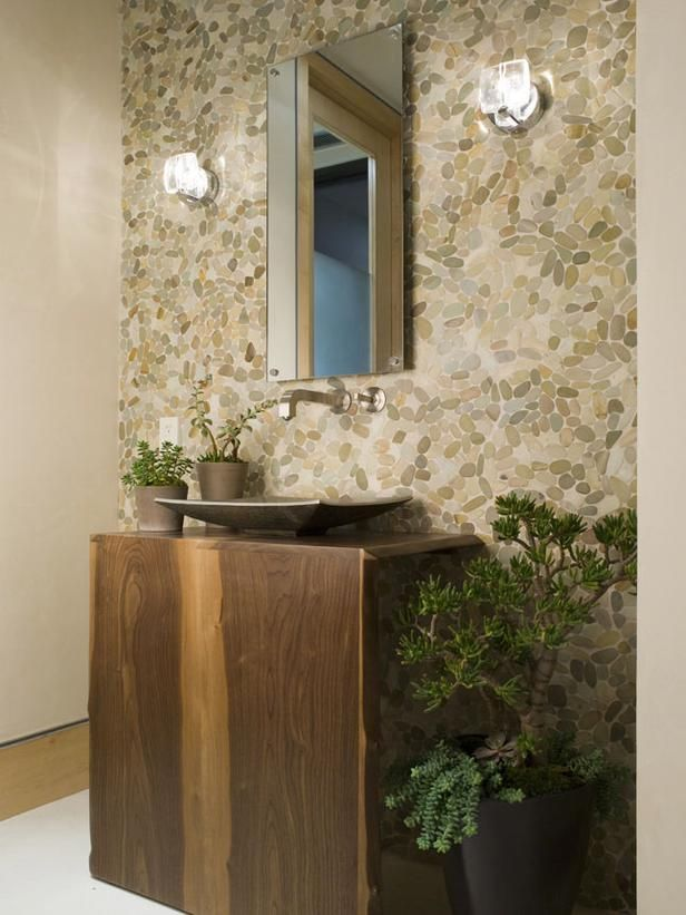 Organic Colors    This powder room brings the outdoors inside with reclaimed wood cabinetry, plants and pebble-covered walls. The sconces add a bit of sparkle.