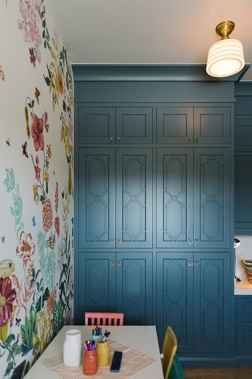 "Fun homework room features a wall clad in floral wallpaper lined with a white play table with drawers lined with colorful chairs situated next to blue cabinets with overlay doors illuminated by Schoolhouse Electric Newbury 4"" flush mount."