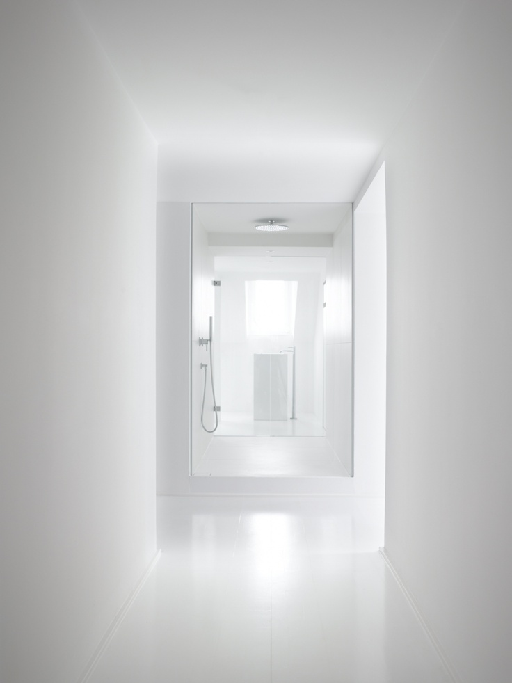 All-white bathroom inside this apartment in Wiesbaden by Christ Christ architects.