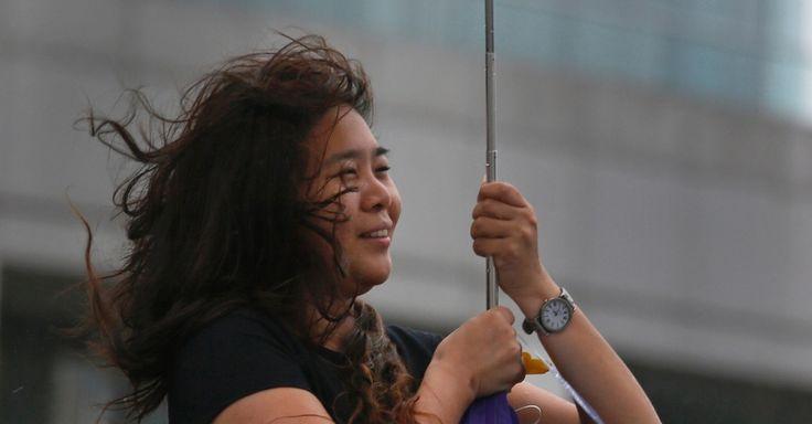 """Mulher tenta se proteger com guarda-chuva durante fortes ventos provocados pela aproximação do tufão Usagi em Hong Kong, na China. Após matar duas pessoas nas Filipinas e provocar deslizamentos de terra em Taiwan, o Usagi, apelidado de """"supertufão"""" por atingir ventos de até 250 km/h, avança para Hong Kong e províncias do sul da China"""