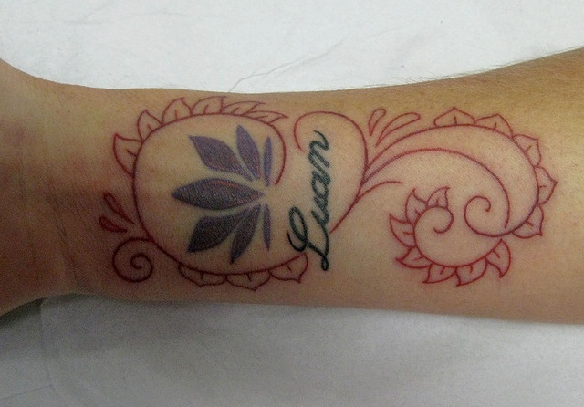 Fiore di loto, nome e cornice rossa: tattoo sul polso