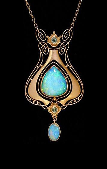 MURRLE BENNETT & Co. (1896-1914). A gold pendant set with a large central opal surrounded by wirework motifs set two peridots and with an opal drop.