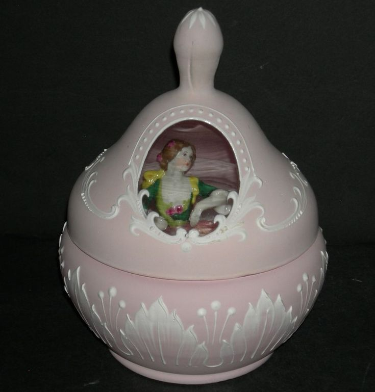 "ANTIQUE - PINK MILK GLASS POWDER BOX w/ 1/2 DOLL PUFF. THREE PIECES - BASE - LID - POWDER PUFF. THE HALF DOLL POWDER PUFF IS 3 1/2"" TOTAL AND THE. HER PINK PLEATED SKIRT HAS THE PUFF ATTACHED AND SHE HAS A PINK. 