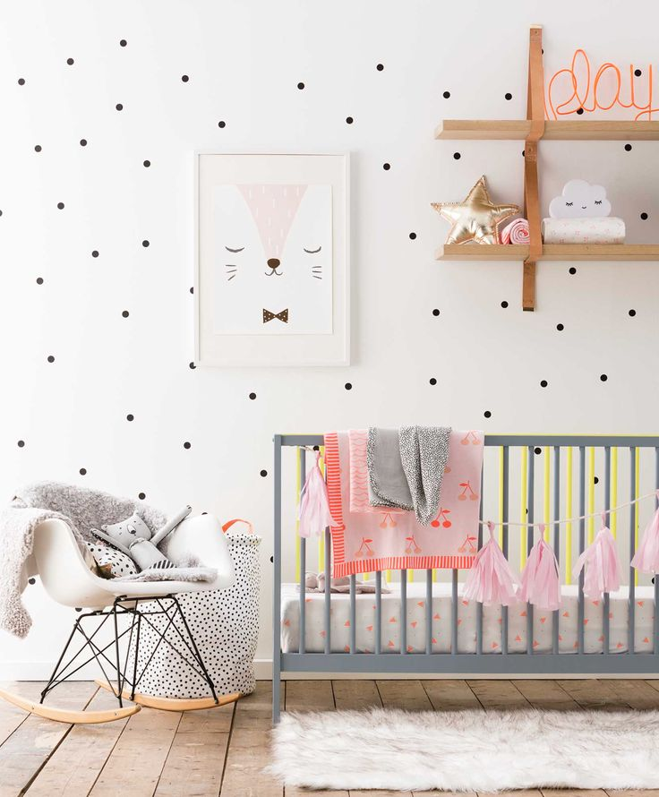 Small black polka dots on the nursery wall, grey crib, white Eames rocking chair and light brown wooden shelves