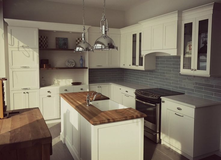 Cuisine blanche de style Cape Cod et mélamine bois foncé. Comptoirs de quartz blanc et bois pour l'ilot. Porte modèle shaker. White Cape Cod style kitchen and dark wood melamine. White quartz countertops and butcher block for the island. Shaker model door.