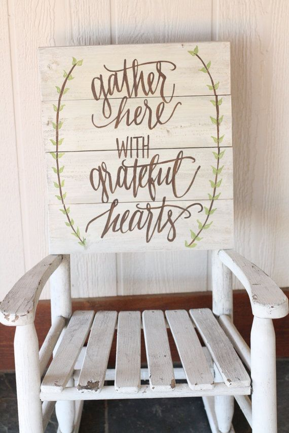 This hand painted wooden sign features a white washed background with brown font and green leaf detail. The phrase Gather Here with Grateful