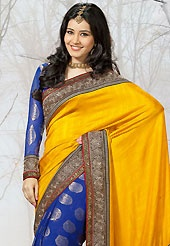 Make a trendy look with this classic embroidered saree. This bright yellow and blue raw silk and viscose saree have beautiful embroidery patch work which is embellished with resham, zari, sequins and lace work. Fabulous designed embroidery gives you an ethnic look and increasing your beauty. Matching blue blouse is available. Slight Color variations are possible due to differing screen and photograph resolutions.