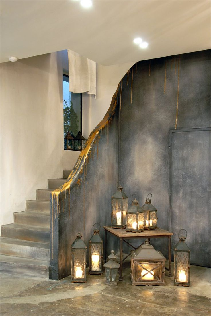 Magical hallway - artisan makes good ... Charcoal distressed wall highlighted with gold, concrete flooring and lanterns a plenty.  Love it