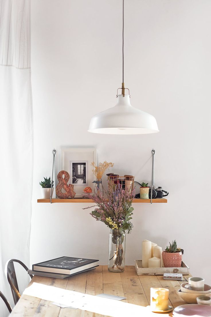 shelf above dining room table | white wall against red wooden furniture