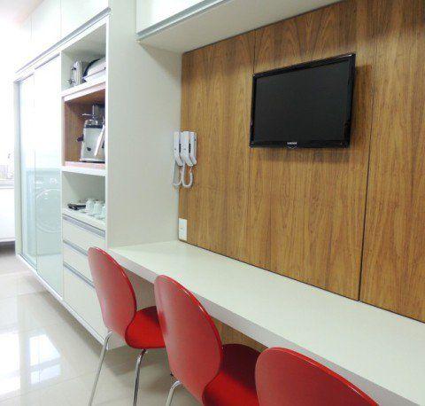 Uma das paredes desta cozinha assinada pelo escritório CS Projetos abriga a área de refeições e um armário. Do outro lado se concentram fogão, pia e geladeira.