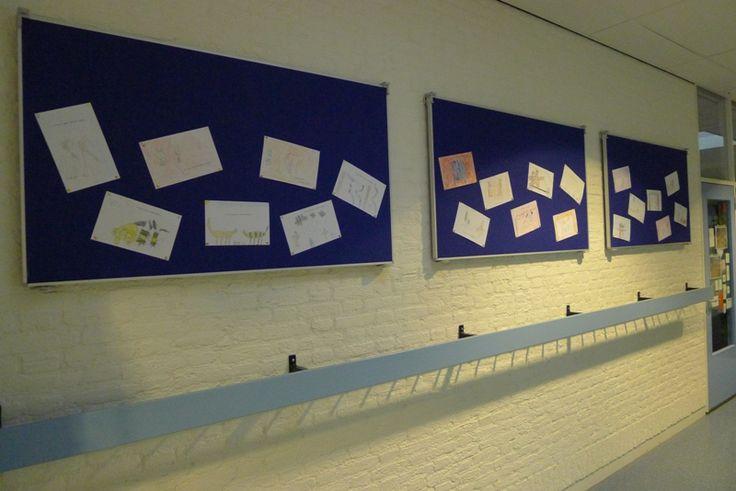 Prikborden in de gang van St. Willibrordus te Middelbeers voor expositie van leerlingenwerk. Voor elke gang een eigen kleur. 4 keer per jaar worden de borden omgedraaid naar de zwarte achtergrond voor het exposeren van een centraal thema.