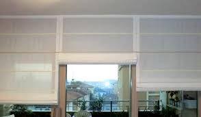Tende a pacchetto con astine, in lino color avorio, applicate a parete con binario a funzione di raccolta verticale.