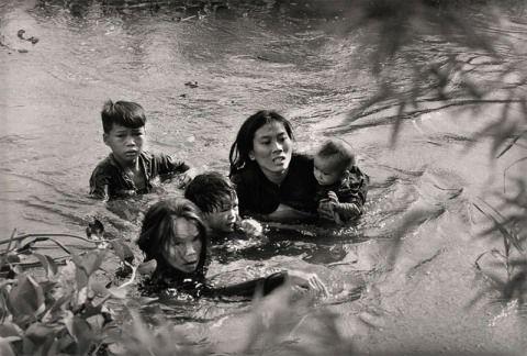 Septiembre, 1965 KYOICHI SAWADA, JAPÓN, UNITED PRESS INTERNATIONAL.  Una madre con sus hijos cruza un rio en Binh Dinht (Vietnam del Sur) para escapar de un bombardeo norteamericano.