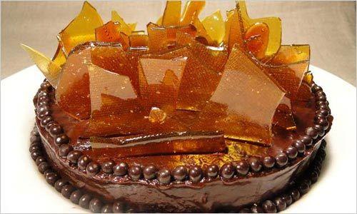 Приготовьте карамель, пергаментную бумагу выложите в форму для запекания, смажьте ее сливочным маслом и вылейте карамель слоем 3-4 мм. Дождитесь полного застывания карамели. Смажьте торт шоколадным кремом, по краям украсьте его арахисом в шоколаде. Разломите карамель на достаточно крупные куски и, устанавливая их вертикально, украсьте торт. Оригинальное украшение торта готово!