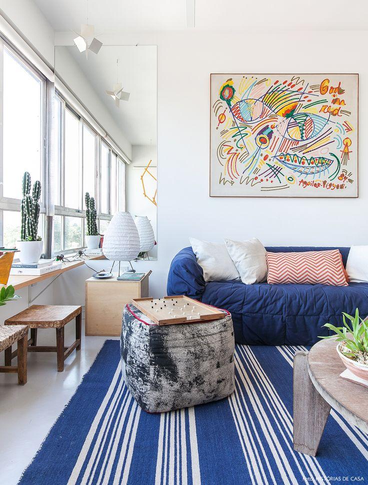 Sala de Estar tem tapete listrado azul, sofá azul marinho,  e móveis de madeira rústica.