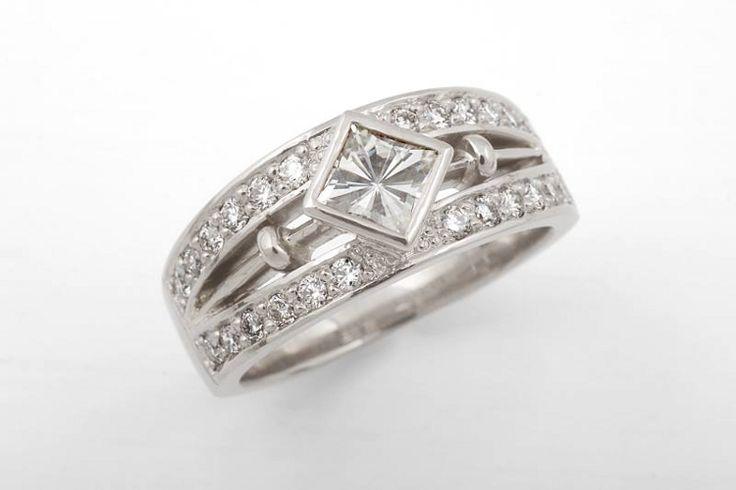 Valkokultaisessa sormuksessa keskellä sädehtii princess-hiottu moissaniitti. Muut kivet timantteja.