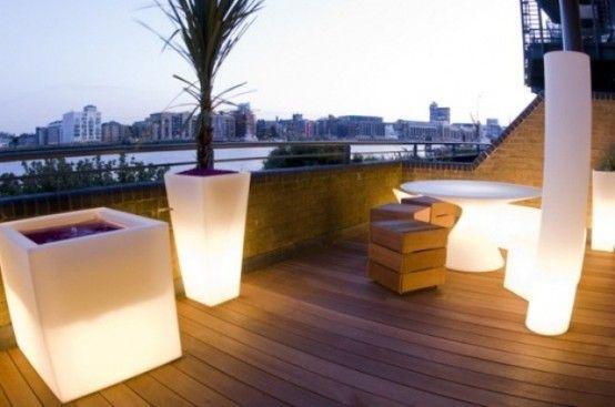 Une terrasse avec de sol en bois et des meubles et des accessoires design en blanc