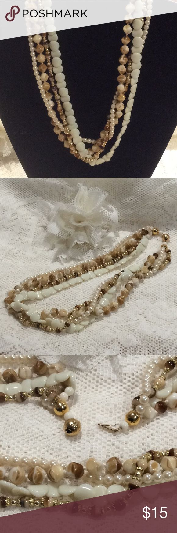 """Fabulous 4 strand necklace! Gorgeous preowned gently used 4 different strand necklace.    Closure works and is signed metal.  Cream, tan, brown and gold tone.   Approx. 8"""" length.  All strands are the same size. Jewelry Necklaces"""