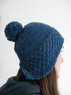 A cute hat that'll keep your ears warm. Knits up quickly in cosy chunky yarn. The double moss stitch band is worked flat, then you join in the round for the stockinette crown. Short row shaping is added for a better fit, keeping your ears cosy! The hat is finished with a simple crochet edging and a pom pom.
