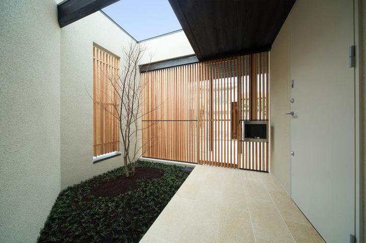 格子の門扉を入ると、玄関の前にささやかな植え込み。<br /> 初夏に新緑を、秋には紅葉を届けるヤマモミジです。<br /> 上部は解放されて、光と雨は樹木に降り注ぎます。<br /> <br /> 玄関を開けると季節を感じるスペースです。 専門家:古前極が手掛けた、ポーチ(Quartz)の詳細ページ。新築戸建、リフォーム、リノベーションの事例多数、SUVACO(スバコ)